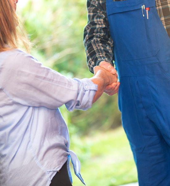 Repairman shaking hands with female customer, light effect